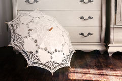 Vintage umbrella against a dresser Stock Image