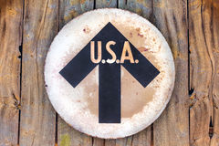 Vintage USA direction sign. Hanging on an old wooden wall royalty free stock images
