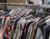 Vintage used clothes in the outdoor flea market. Many vintage clothes in the outdoor flea market stock photos