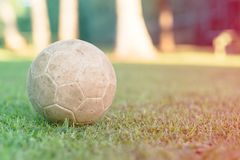 Vintage used soccer ball lying on the grass in park, in the shadow. Trees in the background are in the sun, Rio de Janeiro. Colore. Vintage used soccer ball royalty free stock images