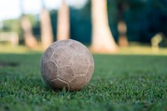 Vintage used soccer ball lying on the grass in park, in the shadow. Trees in the background are in the sun, Rio de Janeiro. Vintage used soccer ball lying on royalty free stock image