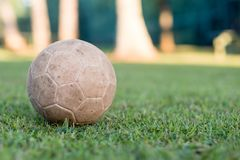 Vintage used soccer ball lying on the grass in park, in the shadow. Trees in the background are in the sun, Rio de Janeiro. Vintage used soccer ball lying on stock images