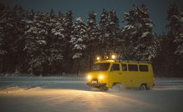 Vintage ussr yellow van winter snow forest. Lights night restauration Royalty Free Stock Photo