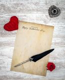 Vintage Valentine`s Day card with red cuddle heart and rose, ink and quill - top view stock photo