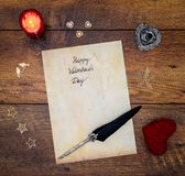 Vintage Valentine`s Day card with red cuddle heart, wooden decorations, red candle and ink and quill on vintage oak - top view royalty free stock images