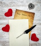 Vintage Valentine`s Day card in withe book with red cuddle hearts ink and quill - top view stock photos