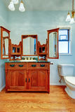 Vintage vanity cabinet with three mirrors in light blue bathroom. Royalty Free Stock Photos