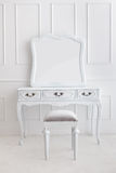 Vintage vanity table set with stool and mirror. Portrait of vintage vanity table set with stool and mirror on white patterned wall stock photo