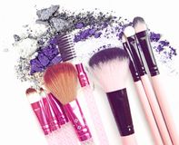 Vintage various makeup brushes isolated over crushed eye shadow. Vintage various makeup brushes isolated over crushed eye shadow royalty free stock photography