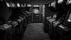 Vintage velho Arcade Video Games em uma sala escura vazia do jogo com luz azul com exposições de incandescência imagens de stock