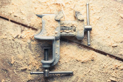Vintage vice tool on wooden background Royalty Free Stock Photos