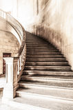Vintage view of marble spiral staircase. Marble winding staircase with high solid handrails in hall leading up. Vintage and grunge view of wide ancient stairway royalty free stock photography
