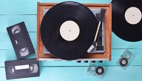 Vintage vinyl player with plates, video cassette, audio cassette on a blue wooden background. Top view. Retro media technologies. Vintage vinyl player with royalty free stock photography