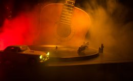 Vintage vinyl record playing on player and acoustic guitar on background with fire orange smoke. Blues concept. With Toy car. Selective focus stock photography
