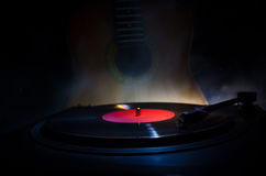 Vintage vinyl record playing on player and acoustic guitar on background with fire orange smoke. Blues concept. Royalty Free Stock Images
