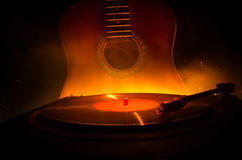 Vintage vinyl record playing on player and acoustic guitar on background with fire orange smoke. Blues concept. Royalty Free Stock Photo