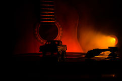 Vintage vinyl record playing on player and acoustic guitar on background with fire orange smoke. Blues concept. With Toy car Stock Photo