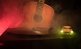 Vintage vinyl record playing on player and acoustic guitar on background with fire orange smoke. Blues concept. With Toy car. Selective focus stock photo