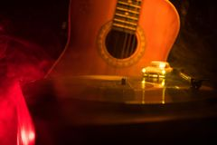 Vintage vinyl record playing on player and acoustic guitar on background with fire orange smoke. Blues concept. With Toy car. Selective focus royalty free stock photo