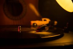 Vintage vinyl record playing on player and acoustic guitar on background with fire orange smoke. Blues concept. With Toy car. Selective focus stock image