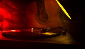 Vintage vinyl record playing on player and acoustic guitar on background with fire orange smoke. Blues concept. With Toy car. Selective focus royalty free stock photography