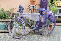 Vintage violet bicycle with flowers and laces Royalty Free Stock Image