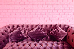 Vintage violet sofa with pink brick wall Royalty Free Stock Photos