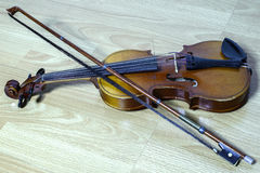 Vintage violin with a bow lies on wooden bench Royalty Free Stock Photos
