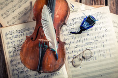 Vintage violin and musical sheets with ink and feather Stock Photos