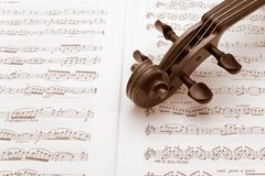 Vintage violin neck resting on a music score. Vintage violin neck resting on a sheet music Stock Image