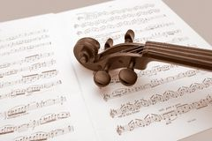 Vintage violin resting over music scores Stock Photos