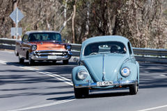 Vintage Volkswagen Beetle driving on country road. Adelaide, Australia - September 25, 2016: Vintage Volkswagen Beetle driving on country roads near the town of stock photo