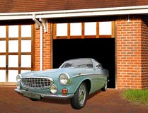 Vintage volvo car in garage. Photo of a blue vintage volvo car on drive coming out of garage stock photography