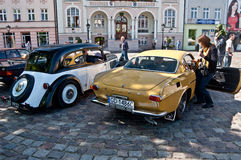 Vintage Volvo P1800 E and Adler automobiles. Classic Swedish beautiful Volvo P1800 E from the sixties and German Adler from the thirties during old cars race in stock images