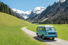 Vintage VW Bully camping car driving on mountain valley road Royalty Free Stock Photo