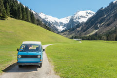 Vintage VW Bully camping car driving on mountain valley road Stock Photography