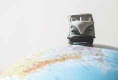 Vintage VW bus on globe. Miniature concept Stock Image