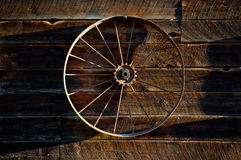 Vintage Wagon. Old wheel hanging on a weathered barn wall Stock Images