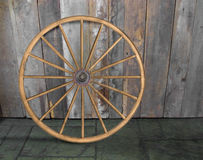 Vintage wagon wheel against wall Royalty Free Stock Photo