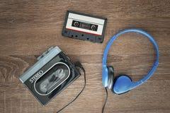 Vintage walkman, cassete and headphones. Vintage walkman, cassete and headphones on the wooden background Stock Photos