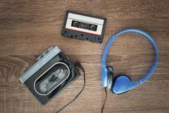 Vintage walkman, cassete and headphones. Vintage walkman, cassete and headphones on the wooden background Royalty Free Stock Images
