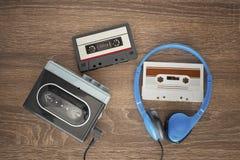Vintage walkman, cassete and headphones. Vintage walkman, cassete and headphones on the wooden background Stock Photo