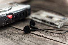 Vintage walkman cassette player with earbuds and tape cassette. Retro style toned image. Selective focus Stock Images