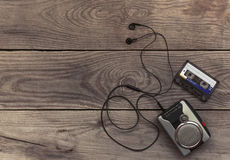 Vintage walkman cassette player with earbuds and tape cassette. Retro style toned image. Selective focus Royalty Free Stock Photo