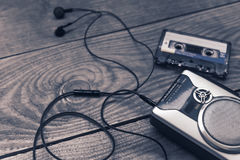 Vintage walkman cassette player with earbuds and tape cassette. Retro style toned image. Selective focus Stock Photos