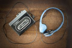 Vintage walkman and headphones. Vintage walkman and headphones on the wooden background stock images