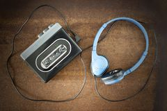 Vintage walkman and headphones. Vintage walkman and headphones on the wooden background Royalty Free Stock Photography