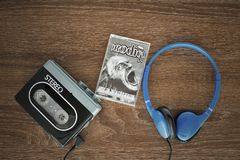 Vintage walkman, the prodigy cassete and headphones. VILNIUS, LITHUANIA - AUGUST 20, 2017: Vintage walkman, the prodigy cassete and headphones on the wooden Royalty Free Stock Image