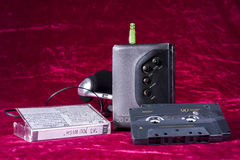 Vintage Walkman with tape. Walkman tape and headphones shot in studio on red silk Royalty Free Stock Photos