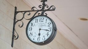 Vintage wall clock on a metal forged bracket on the wall.  stock footage